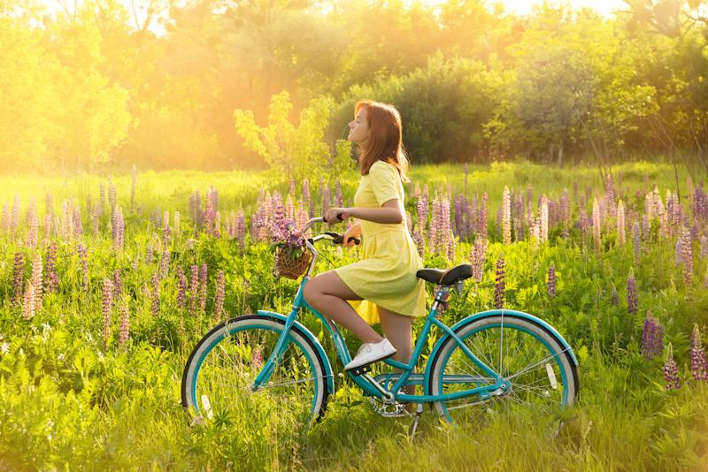 Young teen girl with vintage bike in sunny summer flowered meadow