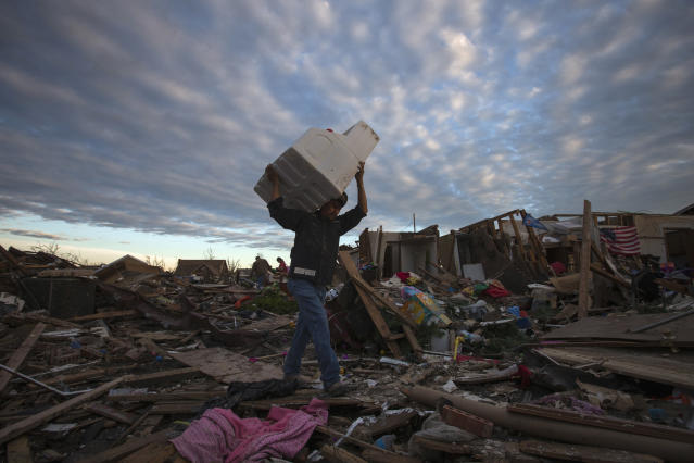 A man carries his belongings through debris after the suburb of Moore, Oklahoma was left devastated by a tornado, on May 21, 2013. Rescuers went building to building in search of victims and survivors picked through the rubble of their shattered homes on Tuesday, a day after a massive tornado tore through the Oklahoma City suburb of Moore, wiping out blocks of houses and killing at least 24 people. REUTERS/Adrees Latif (UNITED STATES - Tags: DISASTER ENVIRONMENT) - RTXZVS5