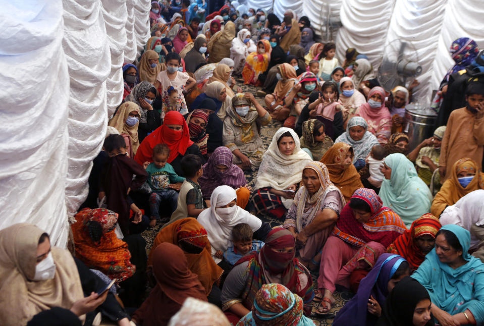 FILE - In this Saturday, April 10, 2021, file photo, women wait to receive food assistance for the upcoming Muslim fasting month of Ramadan, in Lahore, Pakistan. Muslims are facing their second Ramadan in the shadow of the pandemic. Many Muslim majority countries have been hit by an intense new coronavirus wave. While some countries imposed new Ramadan restrictions, concern is high that the month's rituals could stoke a further surge. (AP Photo/K.M. Chaudary)