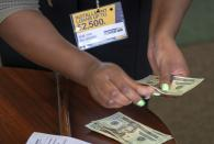 FILE- In this Aug. 9, 2018, photo a manager of a financial services store in Ballwin, Mo., counts cash being paid to a client as part of a loan. The nation's federal financial watchdog has announced its plans to roll back most of its consumer protections governing the payday lending industry. It's the Consumer Financial Protection Bureau's first rollback of regulations under its new Director, Kathy Kraninger, who took over the bureau late last year. California created what supporters called its own nation-leading, state-level version of the federal Consumer Financial Protection Bureau after critics said the Trump administration significantly weakened national protections Friday, Sept. 25, 2020. (AP Photo/Sid Hastings, File)