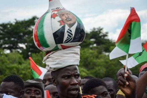 A supporter of Burundi?s ruling CNDD-FDD party balances a gourd on his head with the image of President Nkurunziza at a pre-referendum rally
