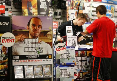 "Game enthusiasts purchase the latest release of ""Grand Theft Auto Five"" after the game went on sale at the Game Stop store in Encinitas, California"