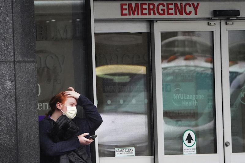 A person stands outside a hospital emergency ward wearing a protective mask following the outbreak of Coronavirus disease (COVID-19), in the Manhattan borough of New York City, New York, U.S., March 23, 2020. REUTERS/Carlo Allegri