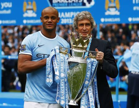 Manchester City's Kompany and manager Manuel Pellegrini pose for pictures with the English Premier League trophy following their soccer match against West Ham United at the Etihad Stadium in Manchester