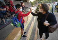 Maksim Mongayt, 7, gives his mother Alexandra Mongayt a high-five before entering his elementary school on the first day of classes in Richardson, Texas, Tuesday, Aug. 17, 2021. Despite Texas Gov Greg Abbott's executive order banning mask mandates by local officials, the Richardson Independent School District and many others across the state are requiring masks for students. (AP Photo/LM Otero)