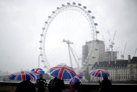 FILE PHOTO: Tourists carrying Union Flag umbrellas shelter from the rain in front of the London Eye wheel in London