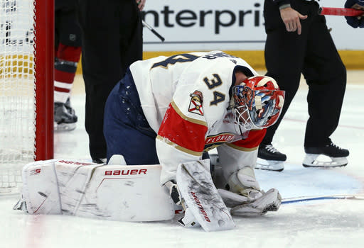 An injured Florida Panthers goaltender James Reimer pauses on the ice during the second period of the team's NHL hockey game against the Arizona Coyotes on Tuesday, Feb. 26, 2019, in Glendale, Ariz. Reimer left the game. (AP Photo/Ross D. Franklin)