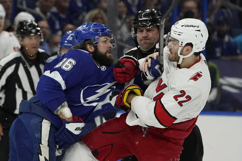 NHL linesman Lonnie Cameron (74) gets between Tampa Bay Lightning right wing Nikita Kucherov (86) and Carolina Hurricanes defenseman Brett Pesce (22) as they battle during the first period in Game 3 of an NHL hockey Stanley Cup second-round playoff series Thursday, June 3, 2021, in Tampa, Fla. (AP Photo/Chris O'Meara)