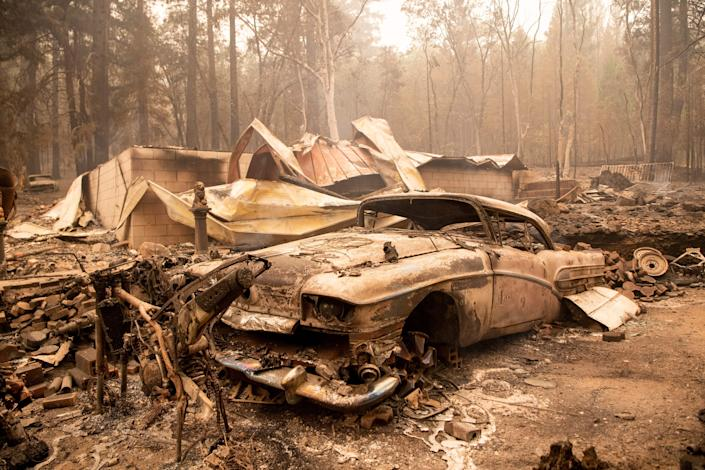A burned classic car sits among the smoldering remains of a home during the Dixie fire in the Indian Falls neighborhood of unincorporated Plumas County, California on July 26, 2021. (Josh Edelson/AFP via Getty Images)