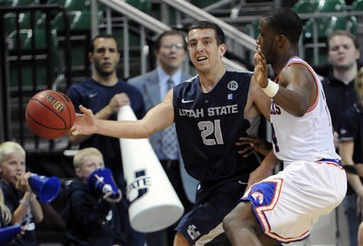 Utah State's Spencer Butterfield (21) passes around UT Arlington's Kevin Butler during the second half of a Western Athletic Conference tournament NCAA college basketball game, Thursday, March 14, 2013 in Las Vegas. UT Arlington won 83-78. (AP Photo/David Becker)
