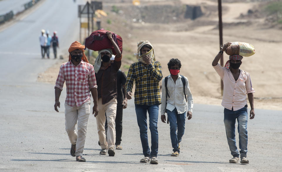 MUMBAI, INDIA - MARCH 30: Migrant workers walk on the Mumbai Nashik highway with their families as they return to their villages, during a 21-day nationwide lockdown to limit the spreading of coronavirus disease (COVID-19), on March 30, 2020 in Mumbai, India.  (Photo by Satyabrata Tripathy/Hindustan Times via Getty Images)
