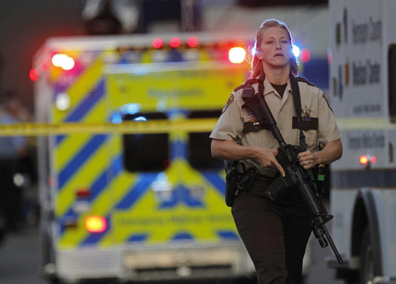 An officer secures the area as police investigate a shooting that left at least two dead and four others wounded at Accent Signage Systems in Minneapolis, Thursday, Sept. 27, 2012. (AP Photo/The Star Tribune, Richard Tsong-Taatarii) MANDATORY CREDIT; ST. PAUL PIONEER PRESS OUT; MAGS OUT; TWIN CITIES TV OUT