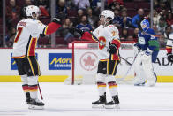 Calgary Flames' T.J. Brodie, left, and Dillon Dube celebrate Dube's goal against Vancouver Canucks goalie Jacob Markstrom, back right, of Sweden, during the second period of an NHL hockey game Saturday, Feb. 8, 2020, in Vancouver, British Columbia. (Darryl Dyck/The Canadian Press via AP)