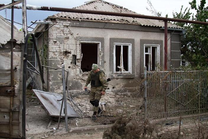A Ukrainian serviceman walks in front of a house damaged by shelling by pro-Russian separatists in the village of Sartana, near Mariupol, Donetsk region, on August 17, 2015 (AFP Photo/Sergey Volski)