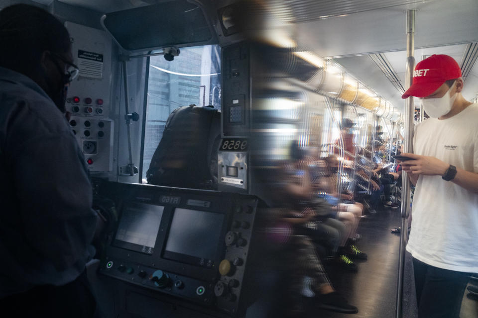 Desmond Hill, a vaccinated MTA conductor, left, operates consoles in the crew cab as passengers riding the N subway line from Brooklyn's Coney Island to Queen's Astoria-Ditmars neighborhoods, Friday, Aug. 13, 2021, in New York. As New York City recovers from the COVID-19 pandemics' peak ridership on the aging transit system continues to rebound as authorities encourage mask and social distancing protocols to stem further transmission of the virus. (AP Photo/John Minchillo)