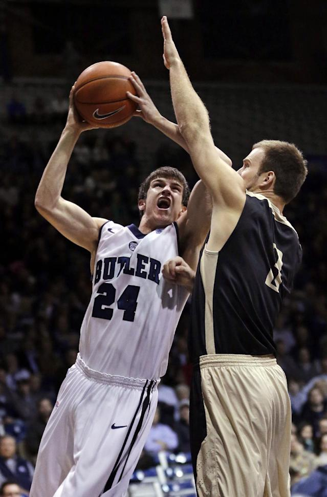 Butler guard Kellen Dunham, left, shoots over Manchester guard Silas Sims in the first half of an NCAA college basketball game in Indianapolis, Monday, Dec. 9, 2013. (AP Photo/Michael Conroy)