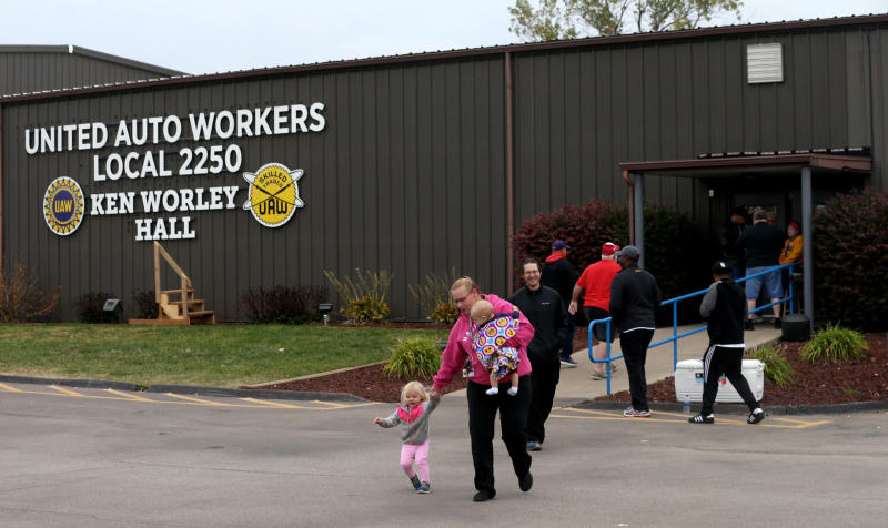 """United Auto Worker Lindsey Higgins, exits the the UAW Local 2250 Ken Worley Hall with her two children after voting on the offer made to union workers by General Motors on Thursday, Oct. 24, 2019, in Wentzville, Mo. """"I don't feel great about the contract but I have these two to think about. I can't keep striking. I've got to keep a roof over their head,"""" said Higgins. UAW workers have been on strike since Sept. 16. (Laurie Skrivan/St. Louis Post-Dispatch via AP)"""