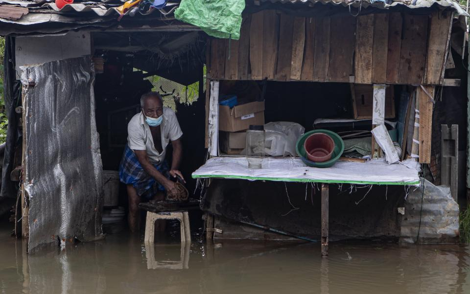 A Sri Lankan man cleans utensils in his stall standing in floodewaters at Malwana, on the out skirts of Colombo, Sri Lanka, Saturday, June 5, 2021. Flash floods and mudslides triggered by heavy rains in Sri Lanka have killed at least four people and left seven missing, while more than 5,000 are displaced, officials said Saturday. Rains have been pounding six districts of the Indian Ocean island nation since Thursday night, and many houses, paddy fields and roads have been inundated, blocking traffic. (AP Photo/Eranga Jayawardena)