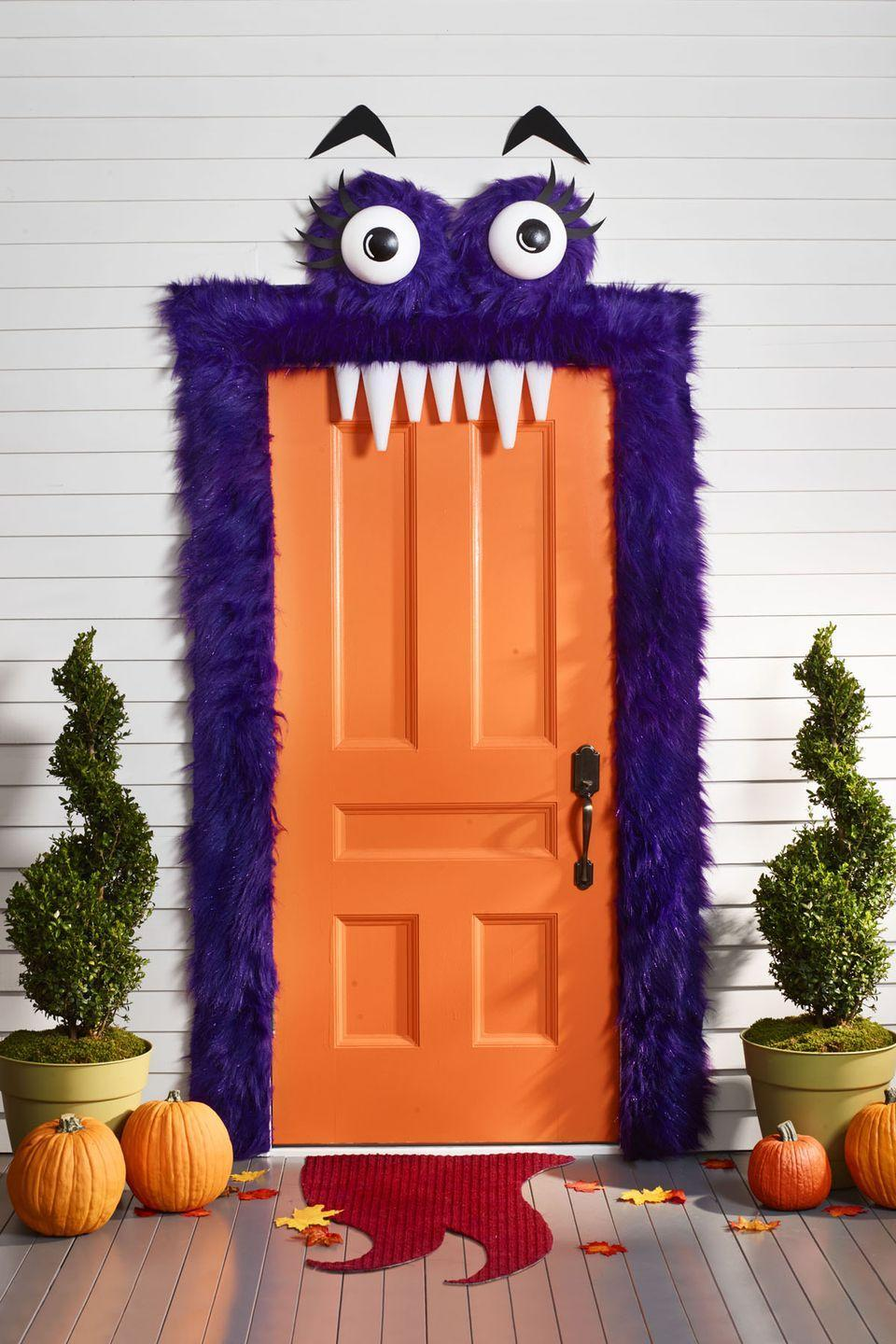 """<p>This adorable purple monster is the perfect way to welcome trick-or-treaters this Halloween.</p><p>1. To make eyes, paint black circles on two 8"""" foam half balls; let dry. Paint white highlight. Cut black foam eyelashes and eyebrows.<br></p><p>2. From 3 yards faux purple fur, cut two 16"""" squares and hot-glue each around a 12"""" foam wreath. Glue eyeballs in center and eyelashes across top. Add a horizontal string across back of each eye for hanging.<br></p><p>3. Frame door with strips of fur using tacks of hem tape. Use Command Hooks to hang eyes above. Tack or hem tape eyebrows in place.<br></p><p>4. For teeth, use foam cones, and then attach to top of door frame with hem tape.<br></p><p>5. Draw and cut tongue shape from floor mat. Spray-paint red; let dry.</p>"""