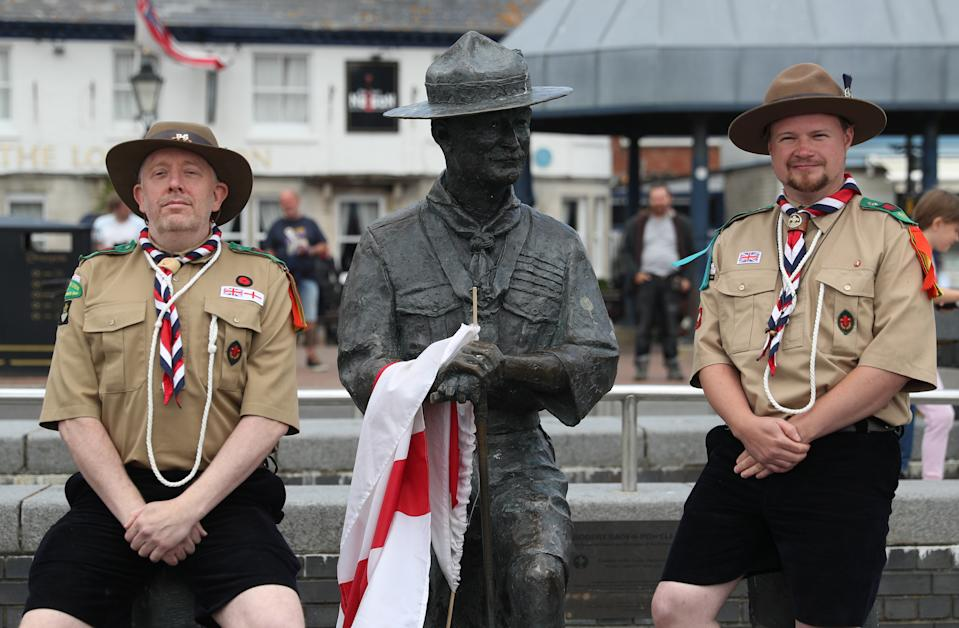 """Rover Scouts Chris Arthur (left) and Matthew Trott pose for a photograph in front of a statue of Robert Baden-Powell on Poole Quay in Dorset ahead of its expected removal to """"safe storage"""" following concerns about his actions while in the military and """"Nazi sympathies"""". The action follows a raft of Black Lives Matter protests across the UK, sparked by the death of George Floyd, who was killed on May 25 while in police custody in the US city of Minneapolis."""