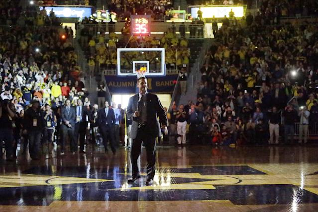 Michiganfootball coach Jim Harbaugh greets fans during halftime of an NCAA college basketball game between Michigan and Illinois in Ann Arbor, Mich., Tuesday, Dec. 30, 2014. (AP Photo/Carlos Osorio)