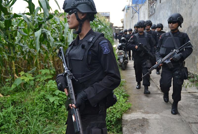 Indonesian police personnel patrol during a raid on the home of a terror suspect in East Java province, in 2016
