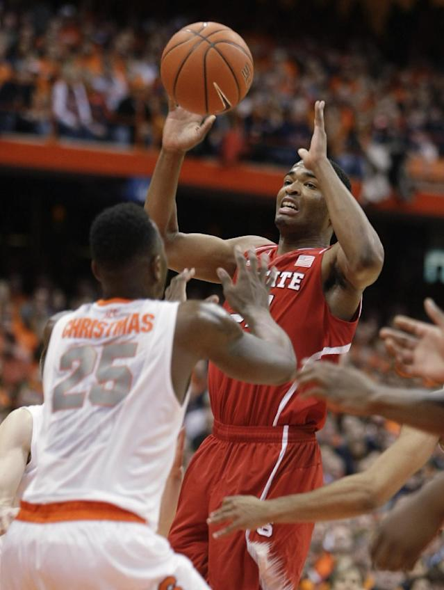 North Carolina State's T.J. Warren, right, looks to pass the ball over Syracuse's Rakeem Christmas, left, during the first half of an NCAA college basketball game in Syracuse, N.Y., Saturday, Feb. 15, 2014. (AP Photo/Nick Lisi)