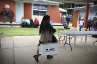 An Indigenous Tzotzil woman walks to set up a voting booth during a non-binding national referendum on whether Mexican ex-presidents should be tried for any illegal acts during their time in office, at the Corazon de Maria community, in Chiapas state, Mexico, Sunday, August 1, 2021. (AP Photo/Emilio Espejel)