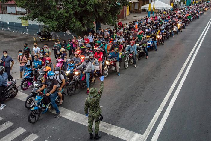 Motorists fall in line at a health checkpoint as authorities begin implementing lockdown measures on March 16, 2020 in San Pedro, Laguna province, on the outskirts of Metro Manila, Philippines. The