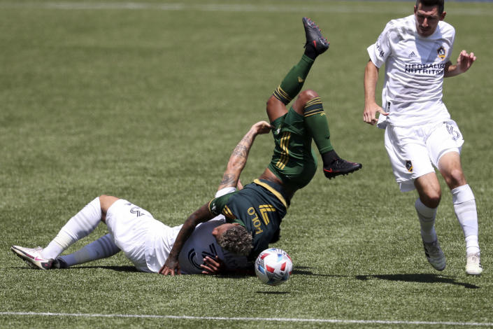 Portland Timbers midfielder Andy Polo (7) flips over LA Galaxy defender Derrick Williams (3) as LA Galaxy midfielder Sacha Kljestan (16) runs alongside them during the first half of an MLS soccer match, Saturday, May 22, 2021, in Portland, Ore. Williams received a red card for the foul. (AP Photo/Amanda Loman)
