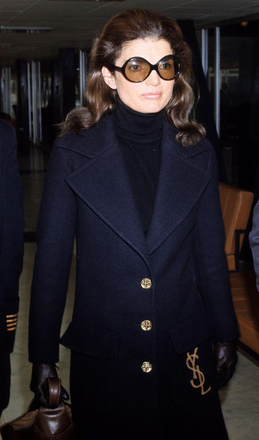 <p>Ready to board a flight at Heathrow Airport, Jackie is the perfect example of 1970s elevated style: a navy turtleneck and wool double-breasted coat paired with sunglasses and leather gloves and handbag all sing together.<br></p>