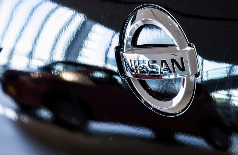 A car is reflected in the bonnet of a Nissan car in the showroom at Nissan's global headquarters in Yokohama south of Tokyo