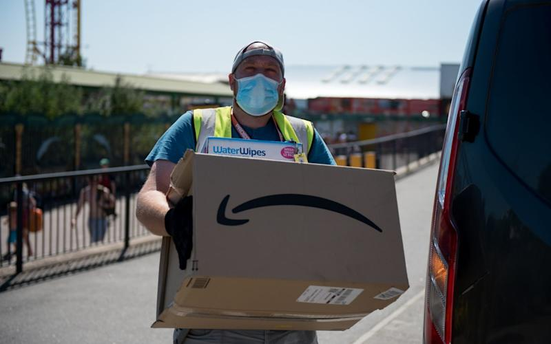 An Amazon delivery person wearing a face mask delivers a parcel  - John Keeble /Getty Images Europe