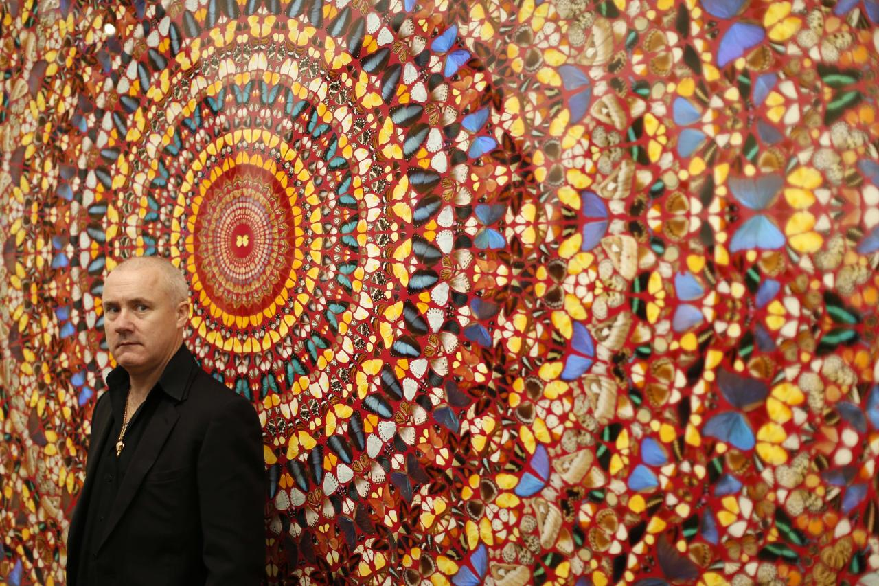 "British artist Damien Hirst stands beside the 2006 piece ""I Am Become Death, Shatterer of Worlds"", butterflies and household gloss on canvas, during a media preview of the first substantial survey show of his work in the UK at the Tate Modern gallery in London, Monday, April 2, 2012. The exhibition, timed for the culmination of the Cultural Olympiad and due to open to the public on Wednesday, showcases over 70 of Hirst's works since he first came to public attention in 1988. (AP Photo/Matt Dunham)"