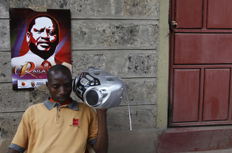 """With a poster of presidential candidate Raila Odinga behind him, a supporter of the Coalition for Reforms and Democracy (CORD) sits outside his house and listens to the results of Kenya's election on his radio in Nairobi, Kenya Thursday, March 7, 2013. Uhuru Kenyatta, presidential candidate of The National Alliance (TNA) is leading in early polls. The coalition of Kenya's prime minister Raila Odinga says the vote tallying process now under way to determine the winner of the country's presidential election """"lacks integrity"""", should be stopped, and the counting process should be restarted using primary documents from polling stations(AP Photo/Sayyid Azim)"""