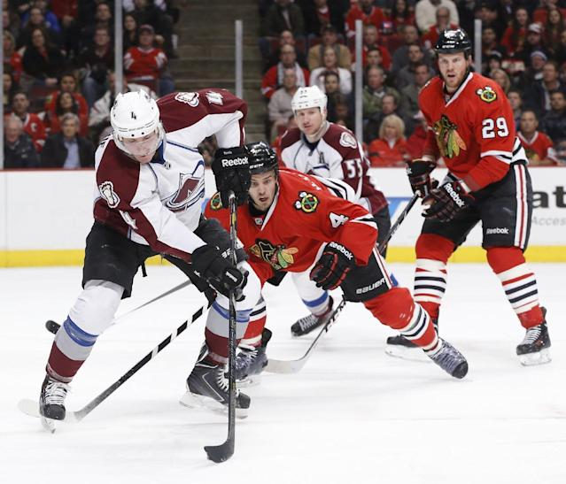 Colorado Avalanche defenseman Tyson Barrie (4) handles the puck in front of the Chicago Blackhawks's goal as defenseman Niklas Hjalmarsson (4) and Bryan Bickell (29) defend during the first period of an NHL hockey game Tuesday, March 4, 2014, in Chicago. Also watching the play is Coilorado's Cody McLeod (55). (AP Photo/Charles Rex Arbogast)