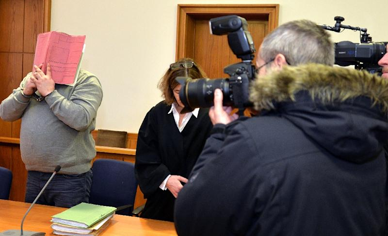 German former male nurse Niels Hoegel (L) hiding his face behind a folder at his last trial faces justice again from Tuesday for allegedly killing 100 people