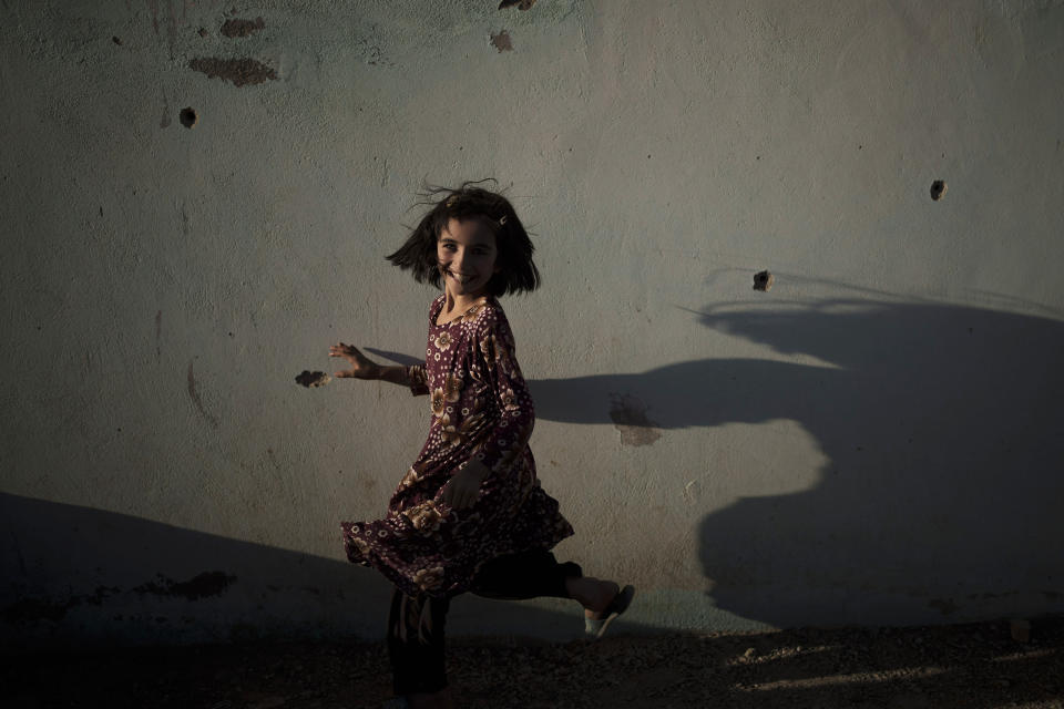 Zahra, 6, plays next to a wall marked by bullet holes at a village in Wardak province, Afghanistan, Monday, Oct. 11, 2021. (AP Photo/Felipe Dana)