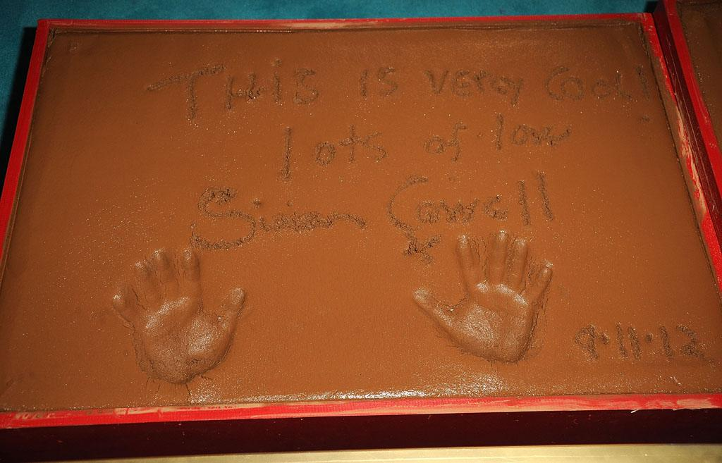"""Simon Cowell leaves a message at the """"The X Factor"""" Season 2 Premiere Party at Grauman's Chinese Theatre on September 11, 2012 in Hollywood, California."""