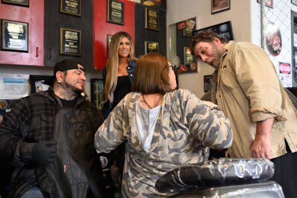Terri Battista, of Myrtle Beach, S.C., shows her completed tattoos to her husband, Joe Battista, at Eternal Ink Tattoo Studio on Nov. 20, 2019, in Hecker, Ill. After a double mastectomy following cancer in 2013, Battista had reconstructive surgery ― but held off on areola tattoos because of the cost. Then she heard about Catalano's shop, where, as a breast cancer survivor, she could get the procedure done for free. (Michael B. Thomas for KHN)