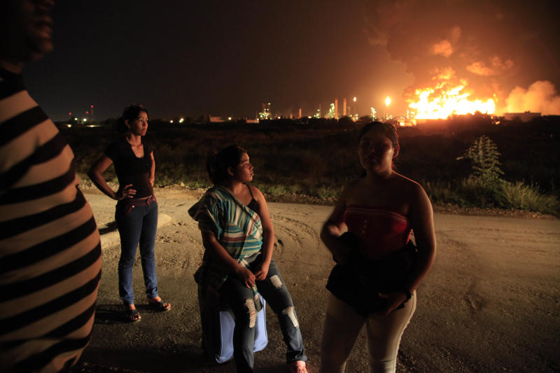 Members of the Cespedes's family stand on the street after they evacuated their house, while fire rises over the Amuay refinery near Punto Fijo, Venezuela, Saturday, Aug. 25, 2012. A huge explosion rocked Venezuela's biggest oil refinery, killing at least 24 people and injuring dozens, an official said. (AP Photo/Ariana Cubillos)