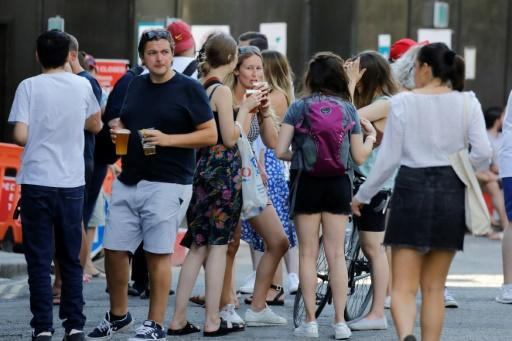 People relax with takeaway beer in plastic cups -- and not much social distancing -- at Borough Market in London