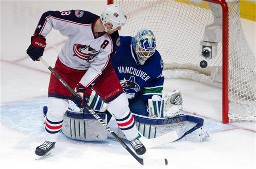 Vancouver Canucks goalie Cory Schneider, right, stops Columbus Blue Jackets' R.J. Umberger during the third period of an NHL hockey game in Vancouver, British Columbia, on Saturday, March 17, 2012. (AP Photo/The Canadian Press, Darryl Dyck)