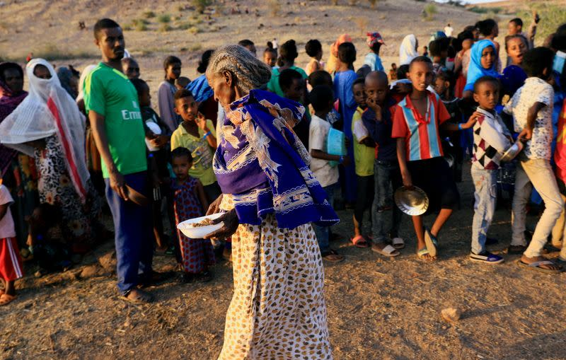An Ethiopian woman who fled war in Tigray region, carries her food ration as others queue at the Um-Rakoba camp on the Sudan-Ethiopia border in Al-Qadarif state