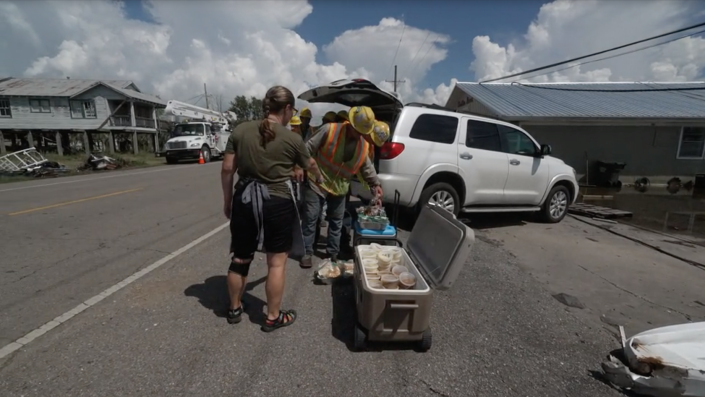 Angel Flood offers linemen free meals that she and other volunteers prepared. / Credit: CBS News
