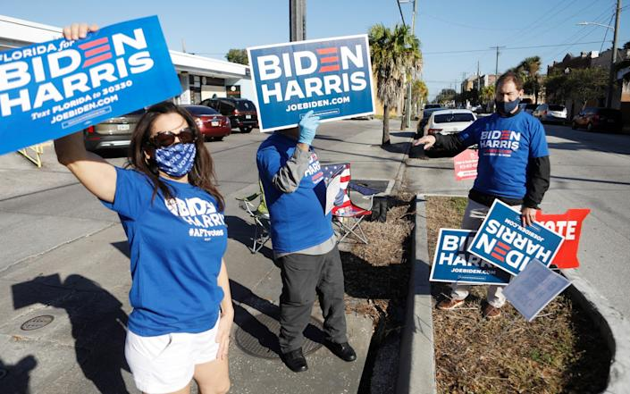 Campaign volunteers wave posters in support of Joe Biden in Tampa, Florida  - Getty Images North America