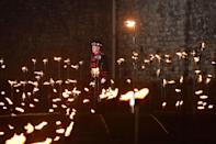 <p>Yeoman Warders (Beefeaters) lighting the first of thousands of flames in a lighting ceremony in the dry moat of the Tower of London as part of an installation called Beyond the Deepening Shadow: The Tower Remembers, to mark the centenary of the end of First World War. (Picture: PA) </p>
