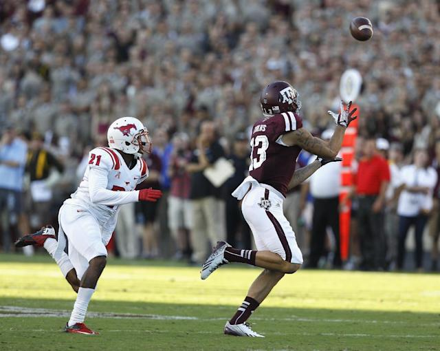 Texas A&M wide receiver Mike Evans (13) completes a reception across the middle as he beats SMU defensive back Kenneth Acker (21) on the play during the first quarter of an NCAA college football game Saturday, Sept. 14, 2013, in College Station, Texas. (AP Photo/Bob Levey)