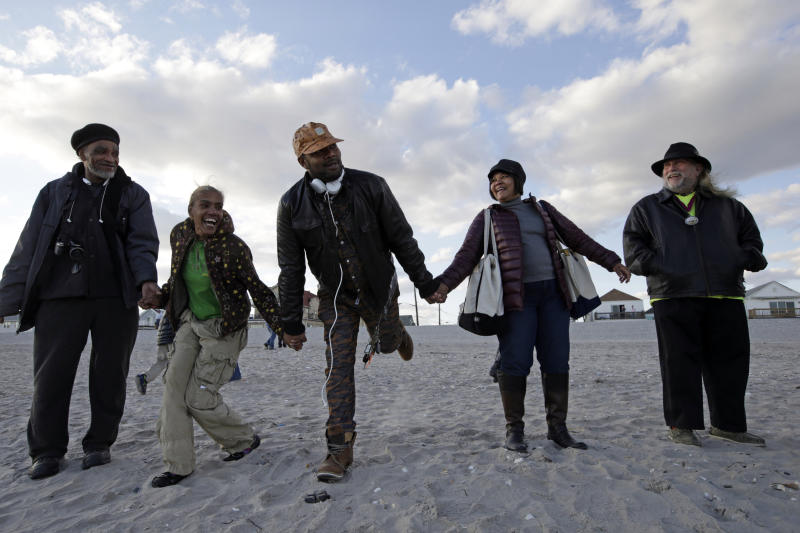 "From left, Thomas Robinson, Debiorah Roman, Carl Myrie and his mother Maureen, join other residents of Arverne on the Sea at they participate in a beachside ceremony ""Rockaways Rising: Hands Across the Sand,"" beach side ceremony commemorating the one year anniversary of Superstorm Sandy, Sunday, Oct. 27, 2013, in New York. The actual one year anniversary of Superstorm Sandy is Tuesday, Oct. 29. (AP Photo/Kathy Willens)"