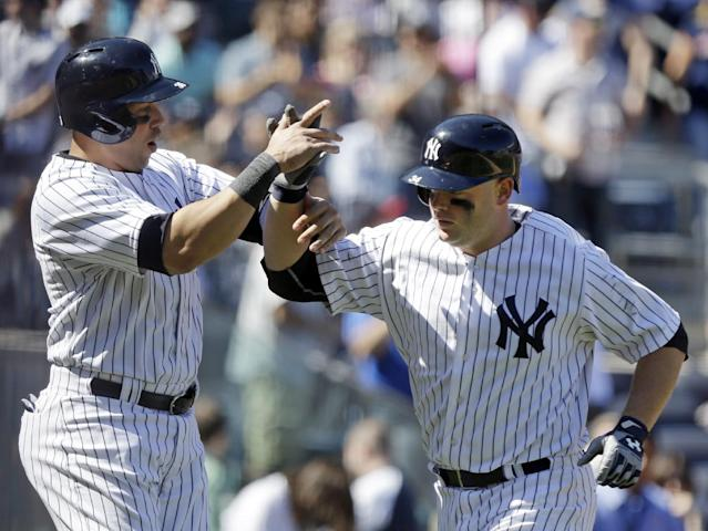 New York Yankees' Carlos Beltran, left, and Brian McCann, celebrate after McCann hit a two-run home run during the sixth inning of a baseball game against the Boston Red Sox Saturday, April 12, 2014, in New York. (AP Photo/Frank Franklin II)